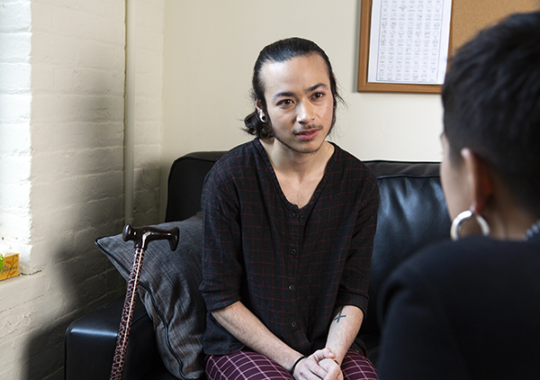 A genderqueer person with a cane sitting on a couch listening